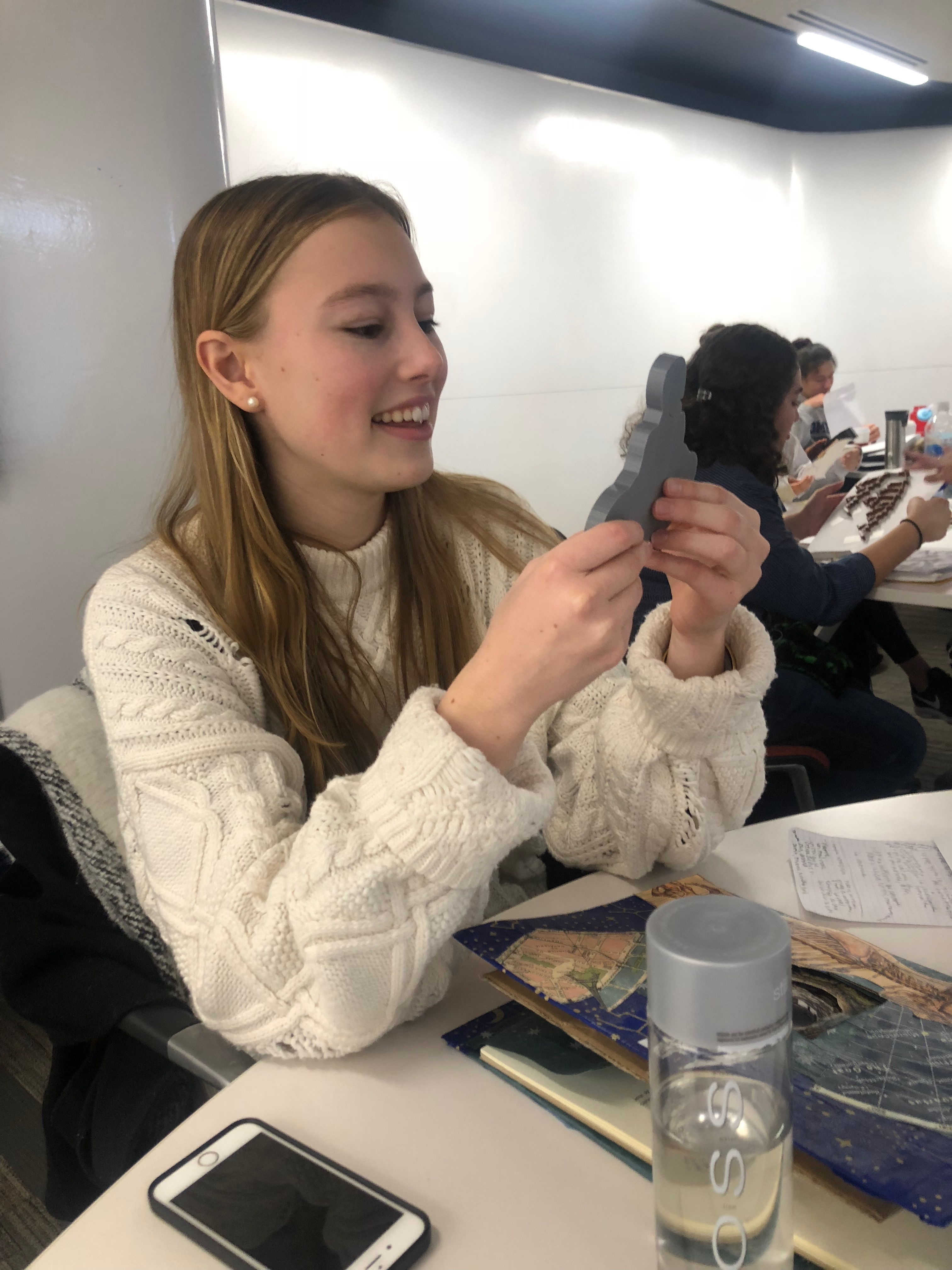 Student smiling while looking at her 3D print