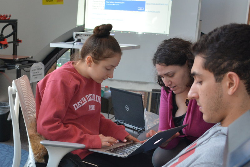 Instructor helping a student convert her 2D design into a 3D file